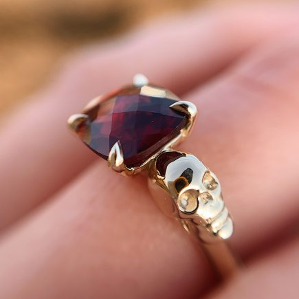 9ct yellow gold and Garnet double-skull ring