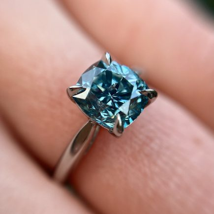 Platinum and cushion-cut treated blue diamond engagement ring